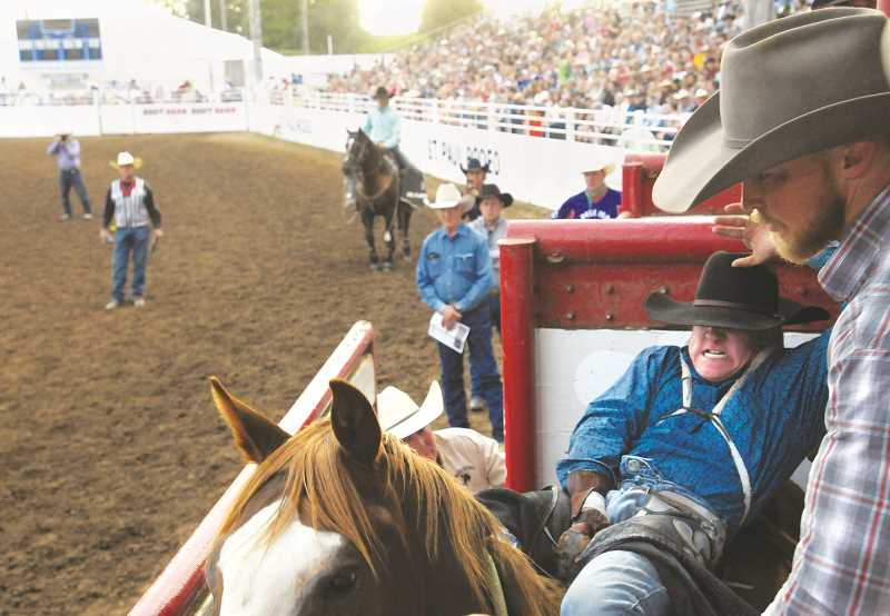 GARY ALLEN - A cowboy prepares in the chutes at St. Paul for his arena appearance.