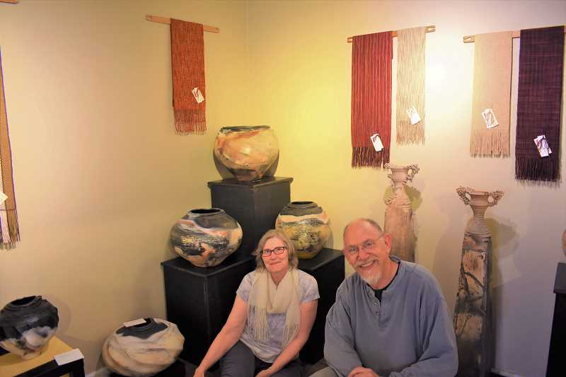 ESTACADA NEWS PHOTO: EMILY LINDSTRAND - Rory Mutton and Michael Berkley sit in the Spiral Gallery surrounded by the pieces they made for their 'Whats Your Story?' show. Mutton created weavings, and Berkley created pottery.
