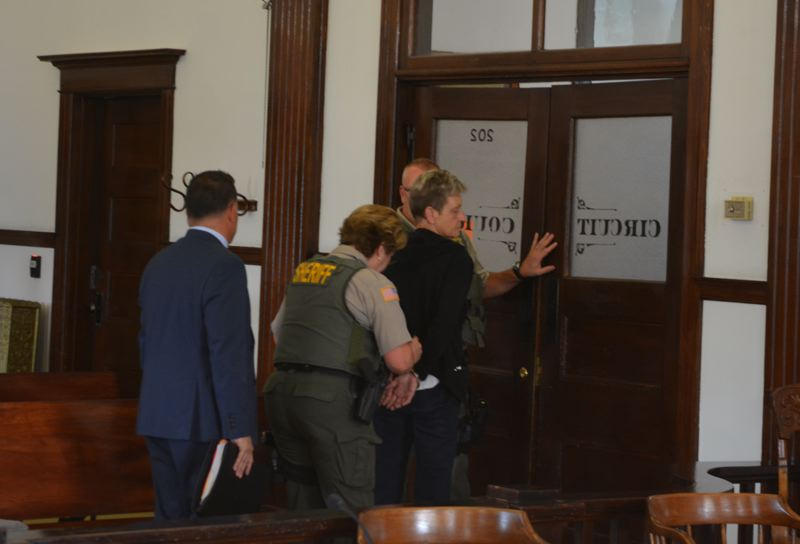 SPOTLIGHT PHOTO: COURTNEY VAUGHN - Linda Hald is escorted out of a Columbia County courtroom in handcuffs Tuesday morning, July 10, after being sentenced to 30 months in prison for an embezzlement case. Hald worked for Columbia County for nearly 30 years.