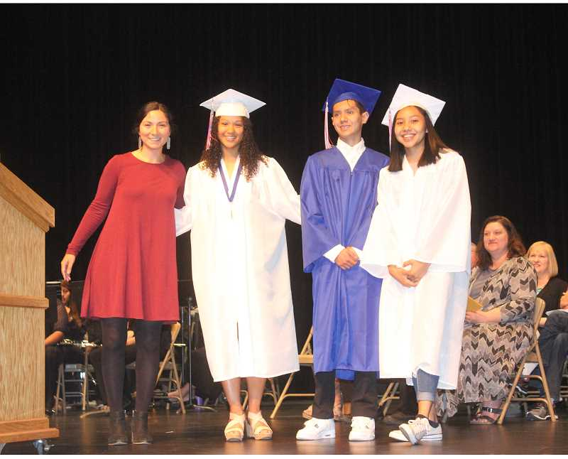 SUSAN MATHENY/MADRAS PIONEER - Dove Spector, left, program coordinator, introduces Warm Springs' first Tribal Health Scholars, Kaliyah Iverson, second from left, Enrique Ramirez and Lynden Harry, at the Madras High School awards assembly, held May 31, two days before graduation ceremonies.