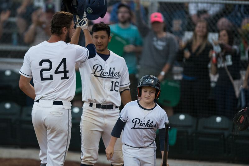 TRIBUNE PHOTOS: KIT MACAVOY - Portland Pickles' player Zander Clarke (left) gets congratulations from Mike Perez during the West Coast League game with the Walla Walla Sweets on Tuesday night. The series continues with 7 p.m. games Wednesday and Thursday.