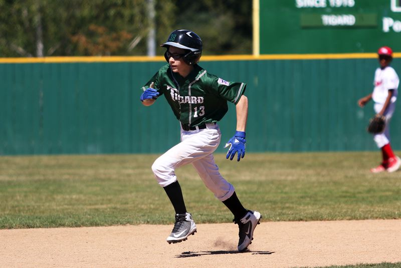 TIMES PHOTO: DAN BROOD - Tigard Little Leagues Campbell Carlberg races to third base on a first-inning triple during Sundays District 4 tournament game.