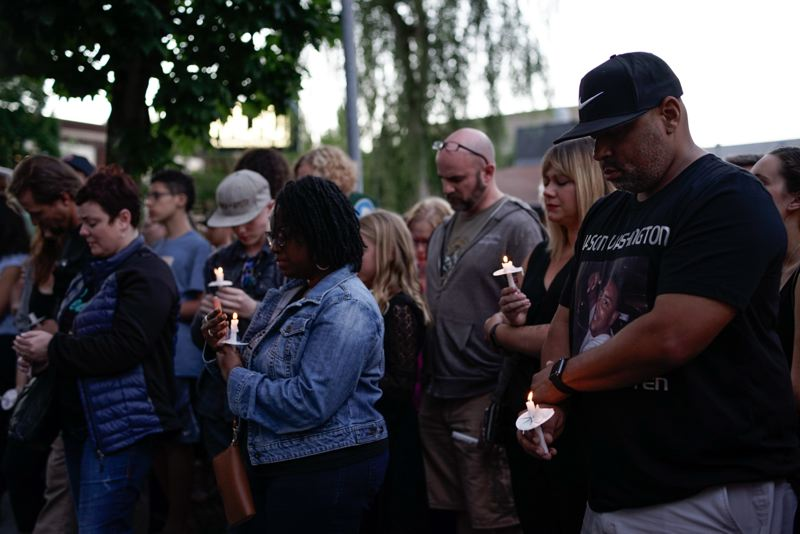 TRIBUNE PHOTO: KIT MACAVOY - Vigil attendees for Jason Washington on Friday, July 6, bow their heads during a prayer.