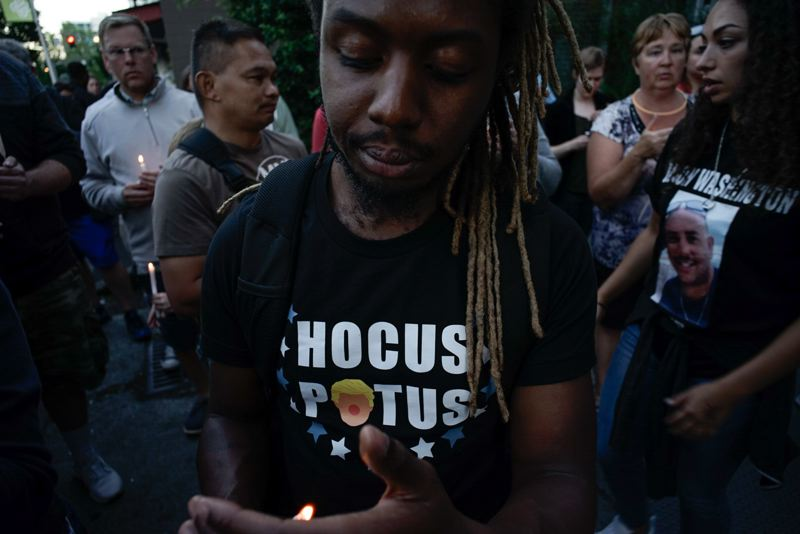 TRIBUNE PHOTO: KIT MACAVOY - Donovan Smith (center) shields his candle from the wind at the start of the vigil on Friday, July 6.
