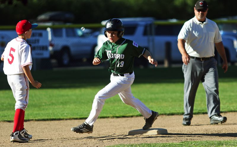 TIMES PHOTO: DAN BROOD - Tigard Little Leagues Michael Harms hits second base and heads to third during play at the ages 9-11 District 4 tournament title game.