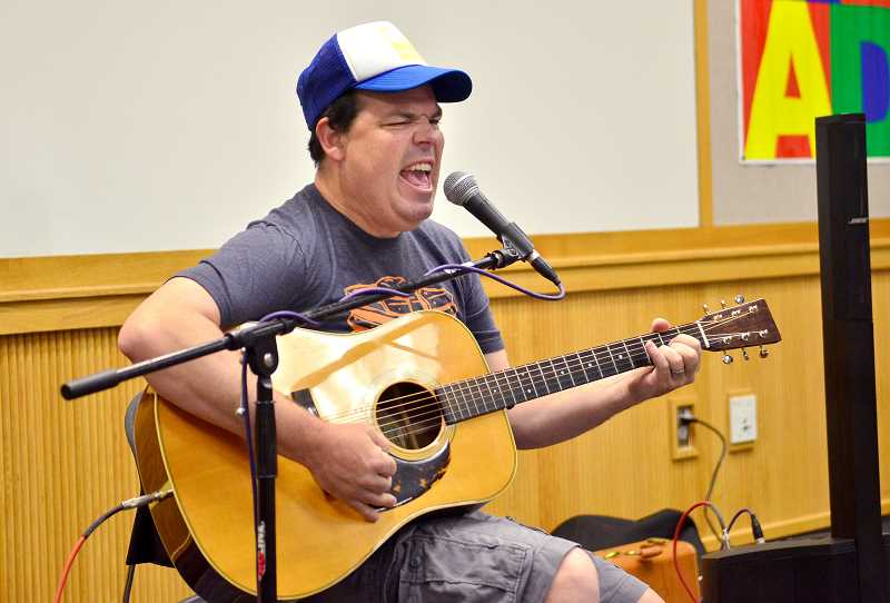 SPOKESMAN PHOTOS: VERN UYETAKE - Mo Phillips entertains the room full of kids with his songs at Wilsonville Public Library June 28.