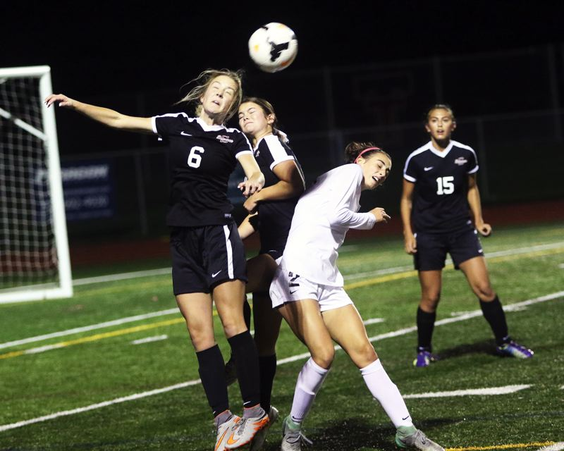 TIMES PHOTO: DAN BROOD - Lauren Scarvie (6) goes up for a header during Sherwoods 3-2 win at Tualatin in a Three Rivers League showdown.