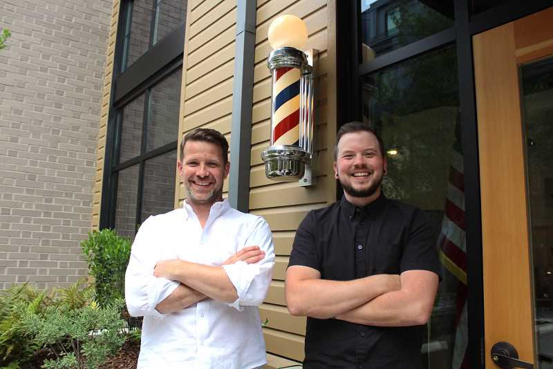 REVIEW PHOTO: SAM STITES - Richard Henry owners Tyler Atkinson and Jeramie Lund pose for a photo with their old school barber pole outside their new shop on the first floor of The Windward.