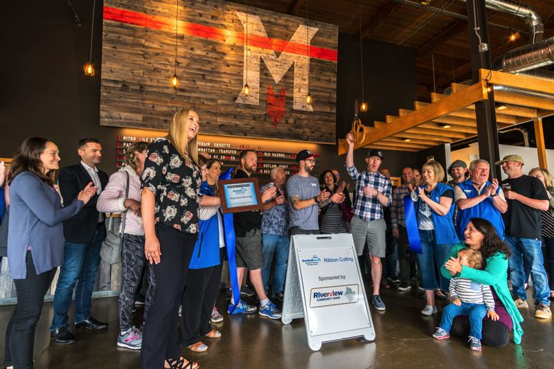 CONTRIBUTED PHOTO: MIGRATION BREWING CO.  - A Gresham Area Chamber of Commerce plaque is presented to Migration Brewing at a ribbon-cutting ceremony for the brewpub in June.
