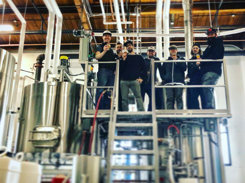 CONTRIBUTED PHOTO: MIGRATION BREWING CO.  - Migration's brew crew and management sample the brewery's first batch on a platform at the new Gresham brewing facility.