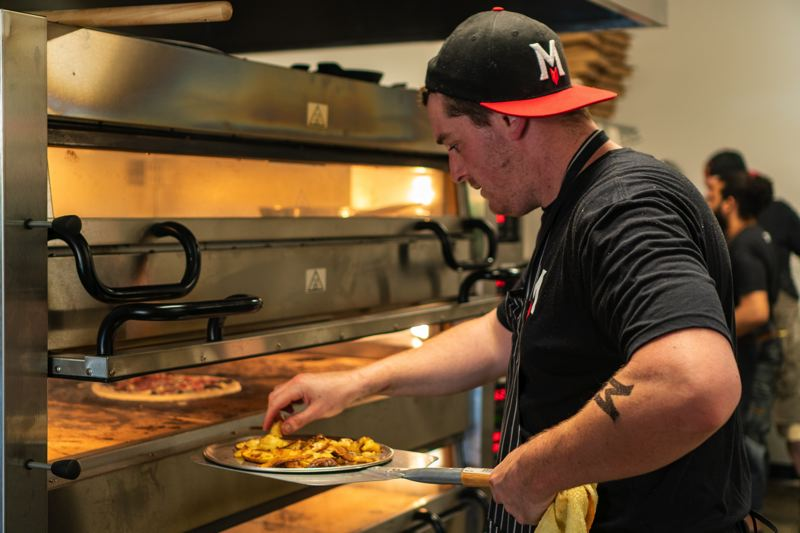 CONTRIBUTED PHOTO: MIGRATION BREWING CO.  - A Migration Brewing cook works on a dish for the pizza oven at Migration Brewing.