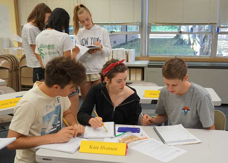REVIEW PHOTO: CLAIRE HOLLEY - Students Will Walsh, Kate Ifverson and Julian White check their answers on a driver's ed quiz.