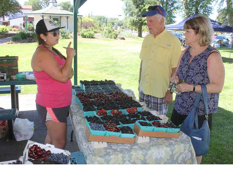 SUSAN MATHENY/MADRAS PIONEER - Polly Burkoff, of D. B. Farmin in Molalla, talks with customers about the different kinds of berries.