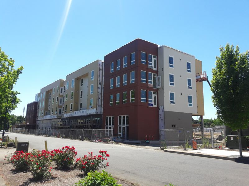 STAFF PHOTO: MARK MILLER - The 78-unit Jesse Quinn Apartments look a lot closer to completion this month after most of the construction wrap covering the outside of the building was removed.