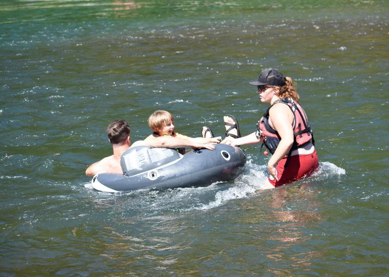 OUTLOOK PHOTO: MATT DEBOW - River floaters Matt and 5-year-old Shay Robinson are guided by American Medical Response Lifeguard Maddie Green as they float the Sandy River at Glenn Otto Community Park on Wednesday, July 11.