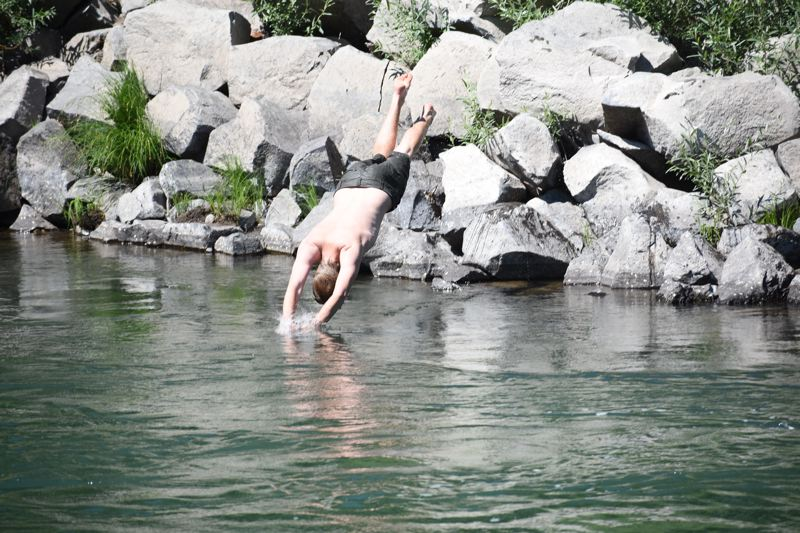 OUTLOOK PHOTO: MATT DEBOW - Simon Kerscher dives into the Sandy River on a hot Wednesday afternoon.