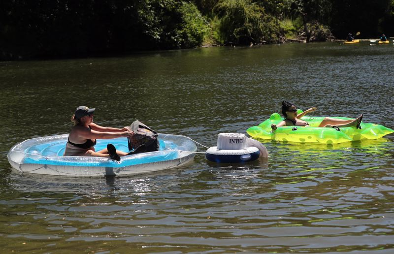 PAMPLIN MEDIA GROUP: JAIME VALDEZ - Sheena Pitcher, left, and Angel Escudero cool off by floating in the Tualatin River near Cook Park in Tigard.