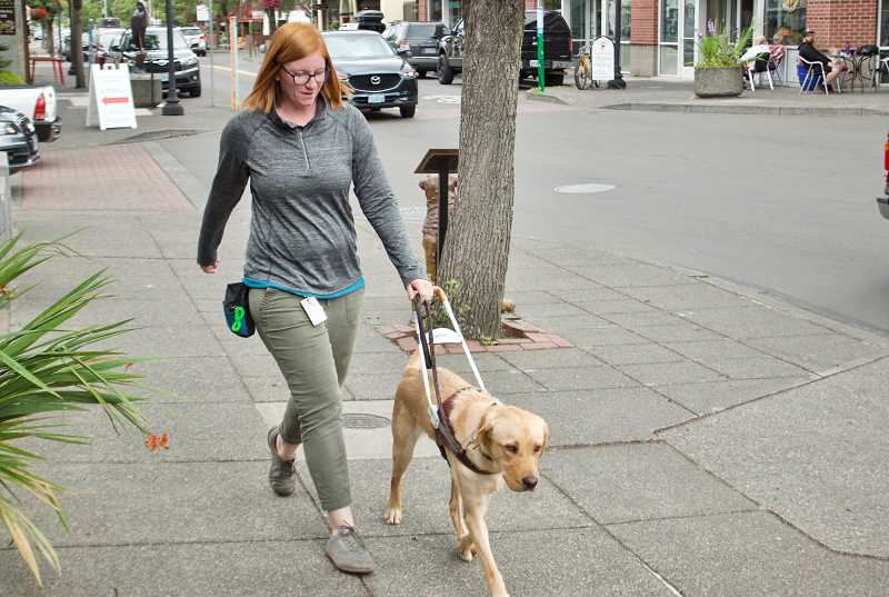 OUTLOOK PHOTO: CHRISTOPHER KEIZUR - Kaitlin Cherney, a trainer with Guide Dogs for the Blind, walks with Dwayne in downtown Gresham, a common spot to teach guide dogs.