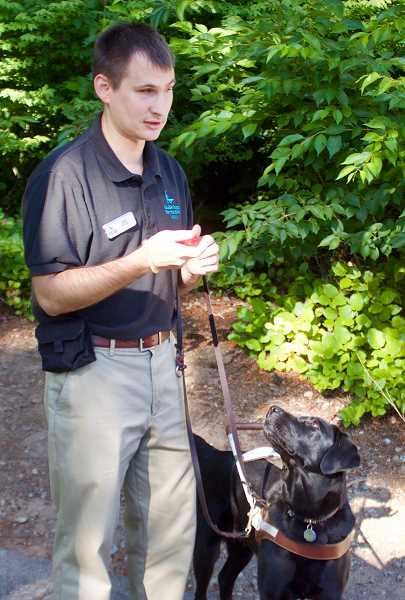 OUTLOOK PHOTO: CHRISTOPHER KEIZUR - Jake Koch, an outreach alumni representative with Guide Dogs, shows off some of the training methods with his dog Forli during a tour of the Boring campus.