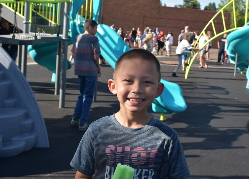 OUTLOOK PHOTO: TERESA CARSON - Second-grader Mason Palma enjoys a green popsicle at the playground ribbon cutting and declared the swings his favorite part of the new equipment.