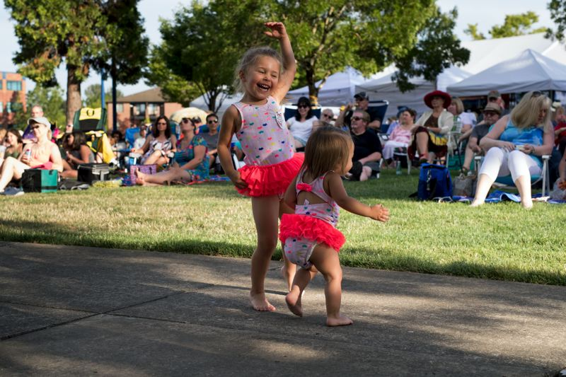 TIMES PHOTO: JAIME VALDEZ - Ava Hawtin, 3-1/2, dances with her sister, Mae, 15 months, to the music by Tom Grant at ArtSplash at the Lake of the Commons.