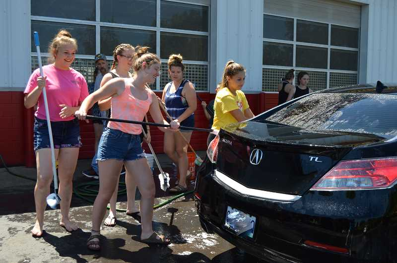 PIONEER PHOTO: CINDY FAMA - The CHS summer softball team washes cars to raise funds for their trip to regionals.