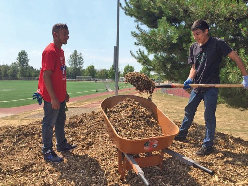COURTESY: WORKSYSTEMS INC. - Miguel Delgado (left) and David Andrade doing weed suppression at Liberty High School, by laying a mulch layer. Scott Crowell from Hillsboro Parks and Recreation was the lead supervisor of this SummerWorks work crew.