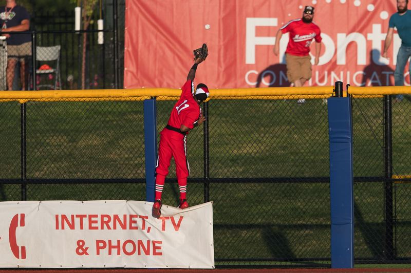 STAFF PHOTO: CHRISTOPHER OERTELL - Hillsboro Hops left fielder Tra Holmes scales the outfield fence in an unsuccessful attempt to pull back a tall home run off the bat of the Boise Hawks' Luke Morgan in the fourth inning Monday, July 16.