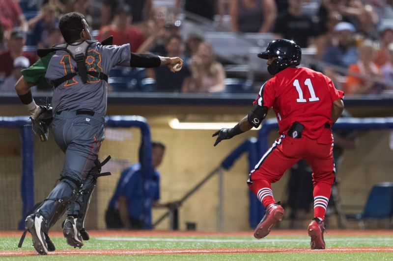 STAFF PHOTO: CHRISTOPHER OERTELL - Boise Hawks catcher Hidekel Gonzalez chases down the Hillsboro Hops' Tra Holmes in a rundown between third base and home plate that erased the Hops' best chances of evening the game up in the eighth inning Monday, July 16.