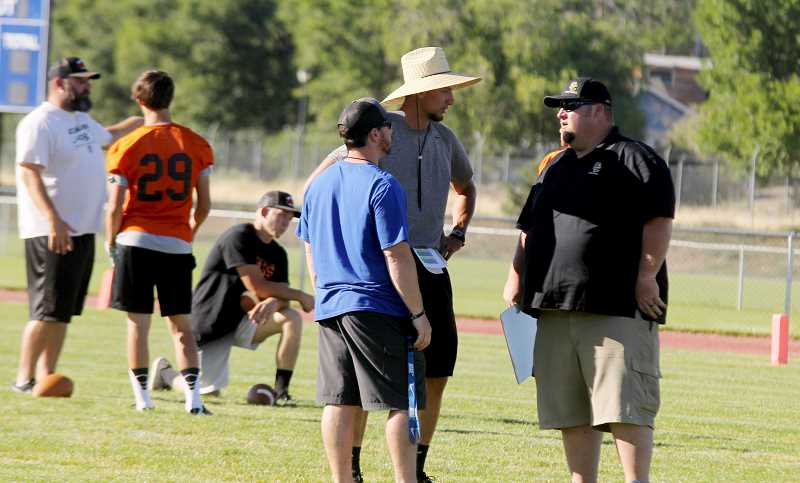 STEELE HAUGEN - Kurt Taylor (left), Jesus Retano (middle) and a Crook County coach talks before a seven-on-seven tournament hosted by Madras.