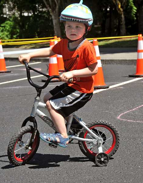 SPOKESMAN PHOTOS: VERN UYETAKE - Matthew Kock, 4, of Wilsonville maneuvers around the bicycle safety course.