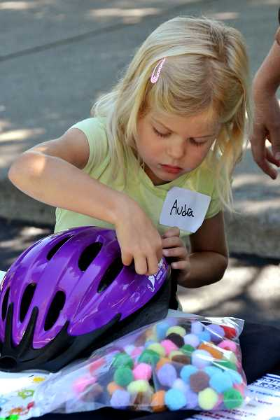 Audra Clark, 5, of Wilsonville decorates her bike helmet at the bike rodeo at Wilsonville Health Fair July 14.