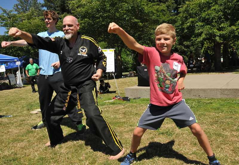 Evan Clark, 8, goes through a martial art drill with member of Lee's Martial Arts School.