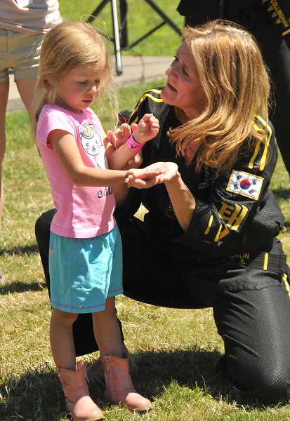 Cora Cameron of Lee's Martial Arts School teaches Evelyn Clark some move.
