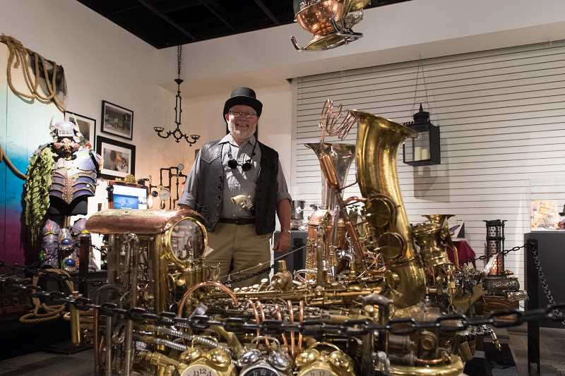 STAFF PHOTO: CHRISTOPHER OERTELL - Artist Chuck Dolence stands next to some of his steampunk sculptures during the unveiling of a steampunk exhibit at the Washington County Museum on July 11.