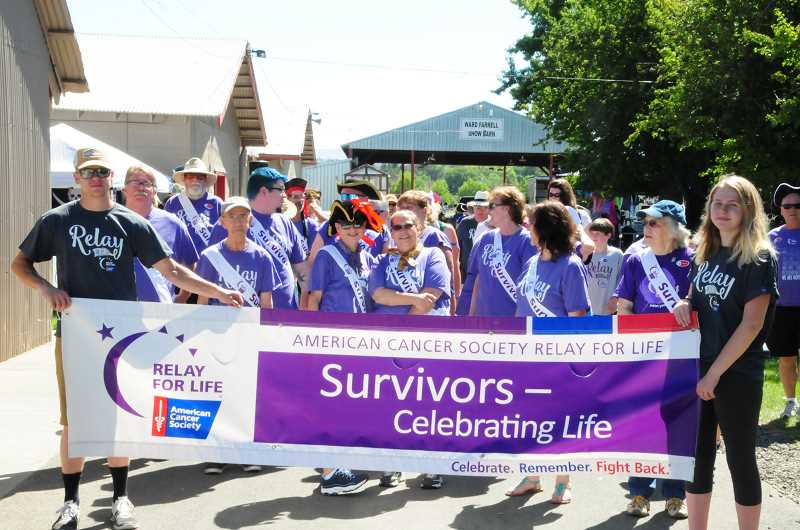 PHOTO BY BILL VOLLMER - Cancer survivors take the first lap around the Jefferson County Fairgrounds Saturday at the Relay For Life event.