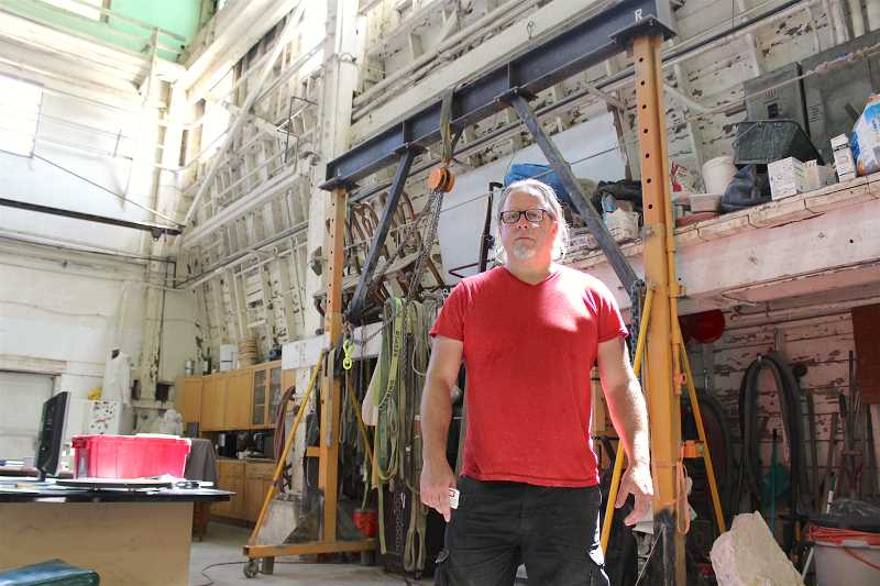 REVIEW PHOTO: SAM STITES - Jason Jones stands in his Northwest Portland studio, where he used a modified construction gantry to restore two beloved Wizer Block mosaics.