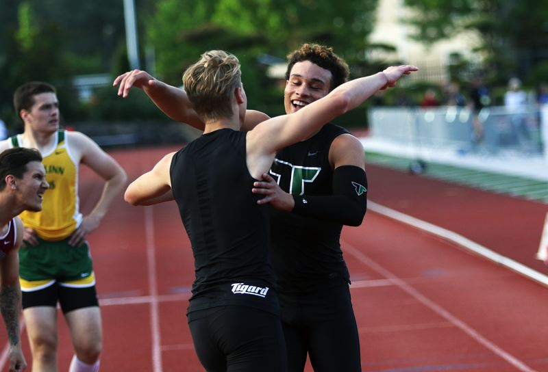 TIMES PHOTO: DAN BROOD - Braden Lenzy (right) hugs fellow Tigard senior Skylar Holloway following his victory in the 400-meter dash at the Three Rivers League district track meet.