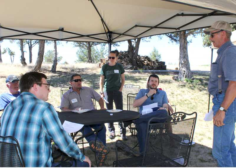 HOLLY M. GILL - Martin Richards, the owner of Fox Hollow Ranch and the chairman of the NUID Board of Directors, talks about farming to a group that included, clockwise from lower left, Jacob Egler, of U.S. Sen. Ron Wyden's office, Gary Harris, NUID Manager Mike Britton, Meriel Darzen, of 1000 Friends of Oregon, and B.J. Westlund, of U.S. Sen. Jeff Merkley's office.