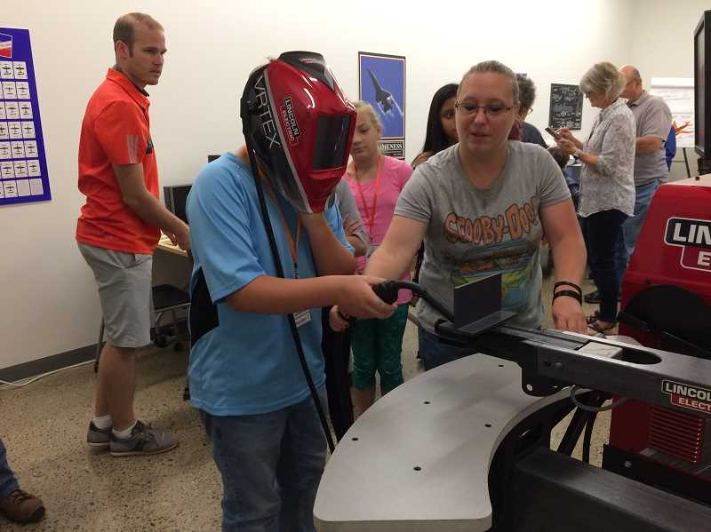 HERALD PHOTO: CAROL ROSEN - Heyden Taylor tries his hand at simulated welding with Marlena Tizo, scoring high for a 12-year old's first turn at welding.