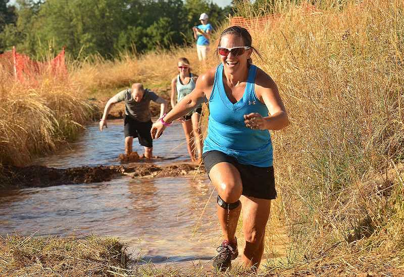 REVIEW FILE PHOTO: VERN UYETAKE - Barb Steinberg was all smiles as she made her way out of a mud pit, one of the obstacles at the 3.1-mile Howl at the Moon Adventure run at Luscher Farm.