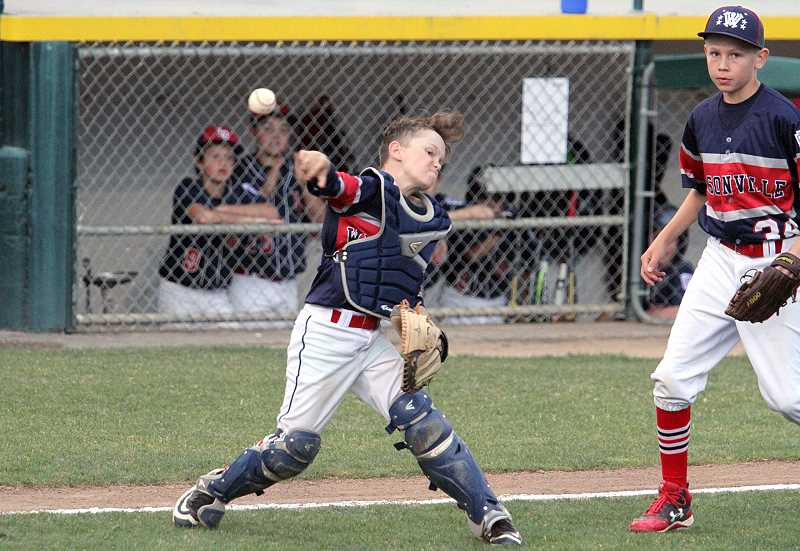 PAMPLIN MEDIA GROUP PHOTO: MILES VANCE - Wilsonville catcher Gunner Gillett throws to first during his teams 11-5 win over Lake Oswego in the District 4 Majors tournament at Alpenrose Dairy Stadium July 9.