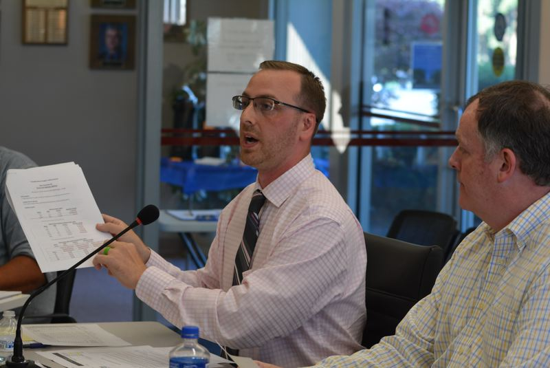 SPOTLIGHT PHOTO: COURTNEY VAUGHN - Matt Brown, left, finance director with the city of St. Helens, holds up a spreadsheet Tuesday evening, July 17, during a Columbia River PUD meeting. Brown and other city officials asked the PUD to reconsider a recent rate hike.