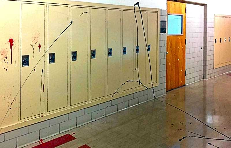 COURTESY OF PORTLAND POLICE BUREAU - The juvenile burglars not only were armed with a loaded gun and were stealing things in the school, they also vandalized the building with paint. All three were arrested.
