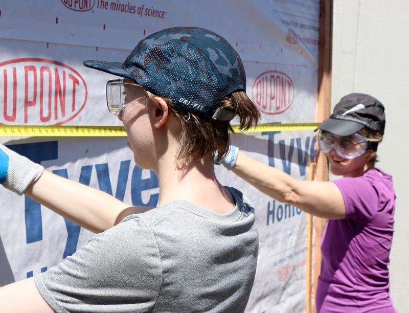 TRIBUNE PHOTO: ZANE SPARLING - Two volunteers measure a wall of a sleeping pod at Right 2 Dream Too in the Lloyd District on Saturday, July 21.