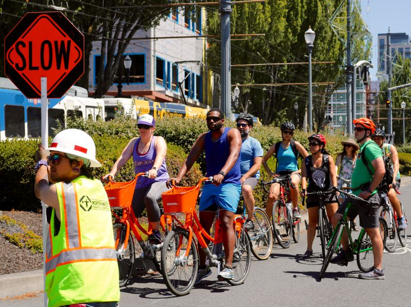 TRIBUNE PHOTO: ZANE SPARLING - Cyclists wait for a crossing guard's permission to keep moving during Sunday Parkways on July 22 in Portland.