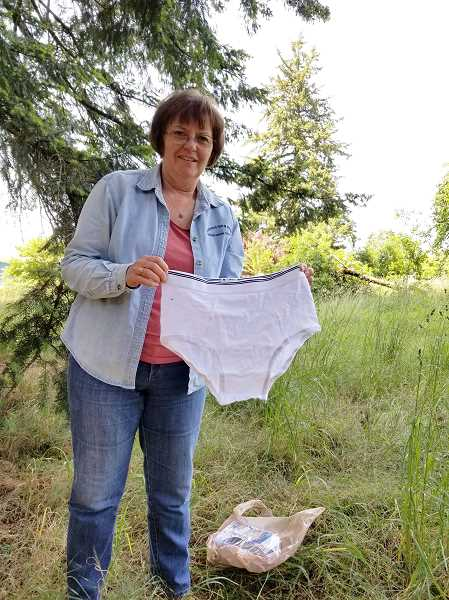 SUBMITTED PHOTO  - Lisa Kilders, education and outreach program manager for the Clackamas Soil and Water Conservation District, holds a pair of 100 percent contton briefs as an example of what to bury to test soil health.