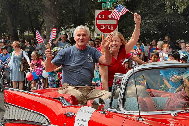 DAVID F. ASHTON - This year's Eastmoreland Neighborhood Independence Day Parade Grand Marshalls - Jerry and Gretchen Eichentopf of Ottos Sausage Kitchen - waved to the crowd, which shortly afterward would be back at Duniway School enjoying the hot dogs the Eichentopfs have always provided.
