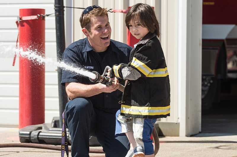 STAFF PHOTO: CHRISTOPHER OERTELL - Hillsboro Tribune photographer Christoper Oertell received a third-place award for best photography for this photo of Tualatin Valley Fire & Rescue spokesman Stefan Myers helping 4-year-old Kazuma Eisenberg with a fire hose during an open house on Aug. 5, 2017.