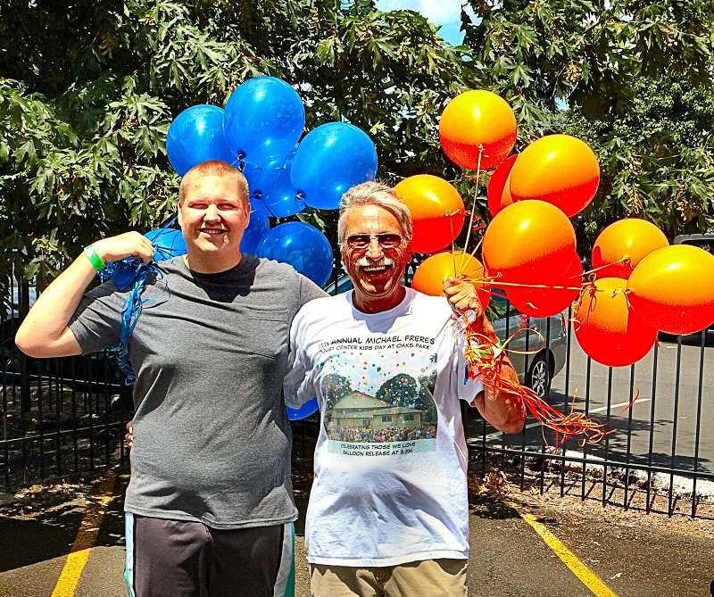 DAVID F. ASHTON - Payton Erickson held balloons, along with his grandfather, Larry Freres, who was the founder of Mikes Kids Day at Oaks Amusement Park. Many balloons were released that that day at The Oaks, in memory of lost loved ones.